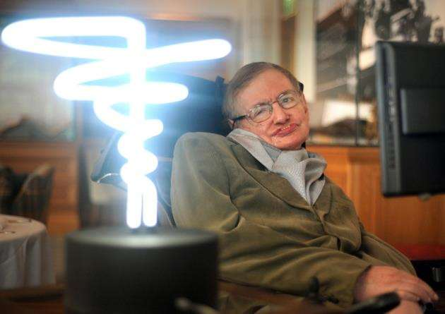 Professor Stephen Hawking beside a lamp titled black hole light by inventor Mark Champkins, presented to him during his visit to the Science Museum in London. Picture: Anthony Devlin