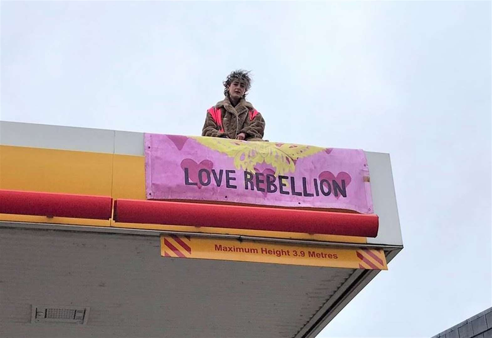 Extinction Rebellion Cambridge Youth members climb on to canopy at Shell garage in latest protest