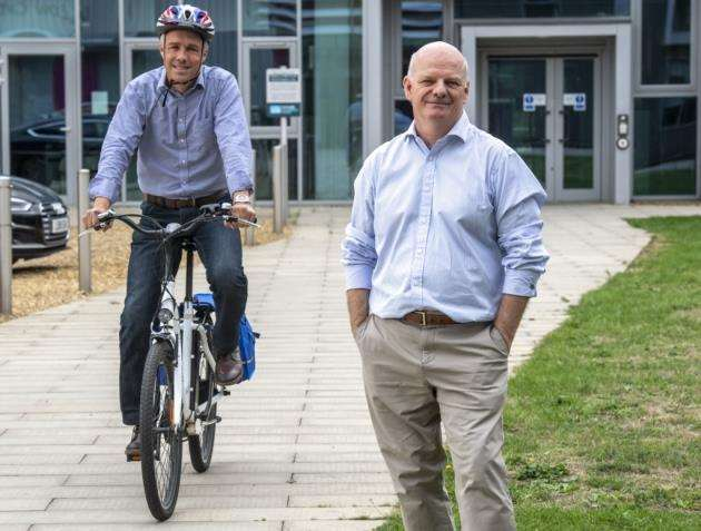 Martin Clarke. director of development & deputy CEO of Allia, uses a Cambridge Electric Transport ebike watched byhead of business Perry Carroll. Picture: Keith Heppell