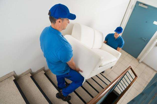 Two movers carrying a sofa on a staircase of a house