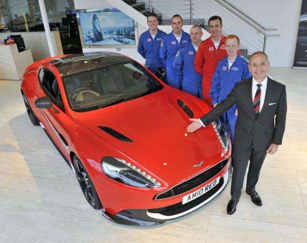 Driving home for Christmas: lucky winner Humphrey Bradley collects the keys for his Aston Martin Vanquish S Red Arrows car at Aston Martin Cambridge from Red Arrows pilot Squadron Leader Adam Collins ( in red flying suit ), Red 10. Photo: Adrian Brooks/Imagewise