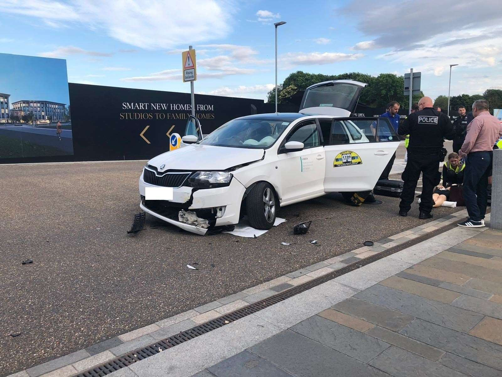 Police and onlookers at Eddington Avenue in Cambridge after Uber car collided with bollard (13731173)