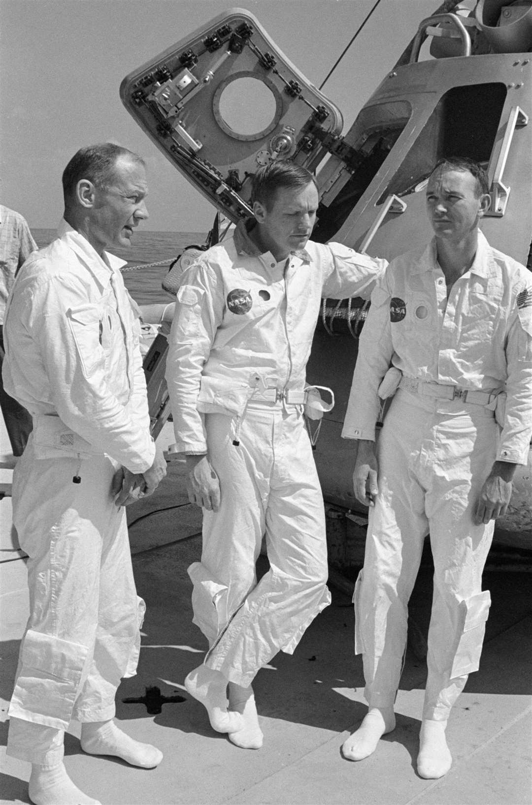 May 24, 1969: The prime crew of the Apollo 11 lunar landing mission relaxes on the deck of the NASA Motor Vessel Retriever prior to participating in water egress training in the Gulf of Mexico. From left are astronauts Edwin E. Aldrin Jr., lunar module pilot; Neil A Armstrong, commander; and Michael Collins, command module pilot. In the background is Apollo Boilerplate 1102 which was used in the training exercise. Image: NASA (14041987)