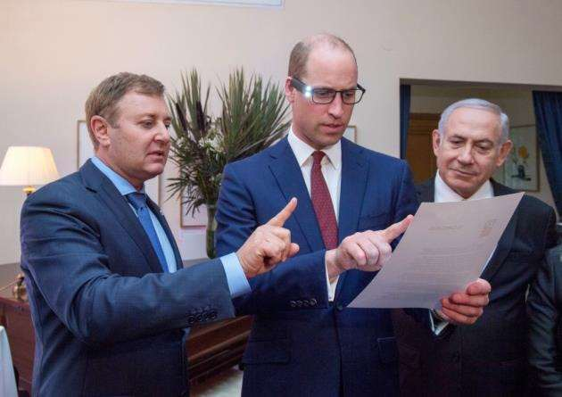 The Duke of Cambridge (centre), with Israeli Prime Minister Benjamin Netanyahu (right) and inventor Ziv Aviram (left) as he tries on the OrCam glasses during a garden reception of the UK Ambassador to Israel in Tel Aviv as part of his tour of the Middle East. Picture: Arthur Edwards/The Sun/PA Wire