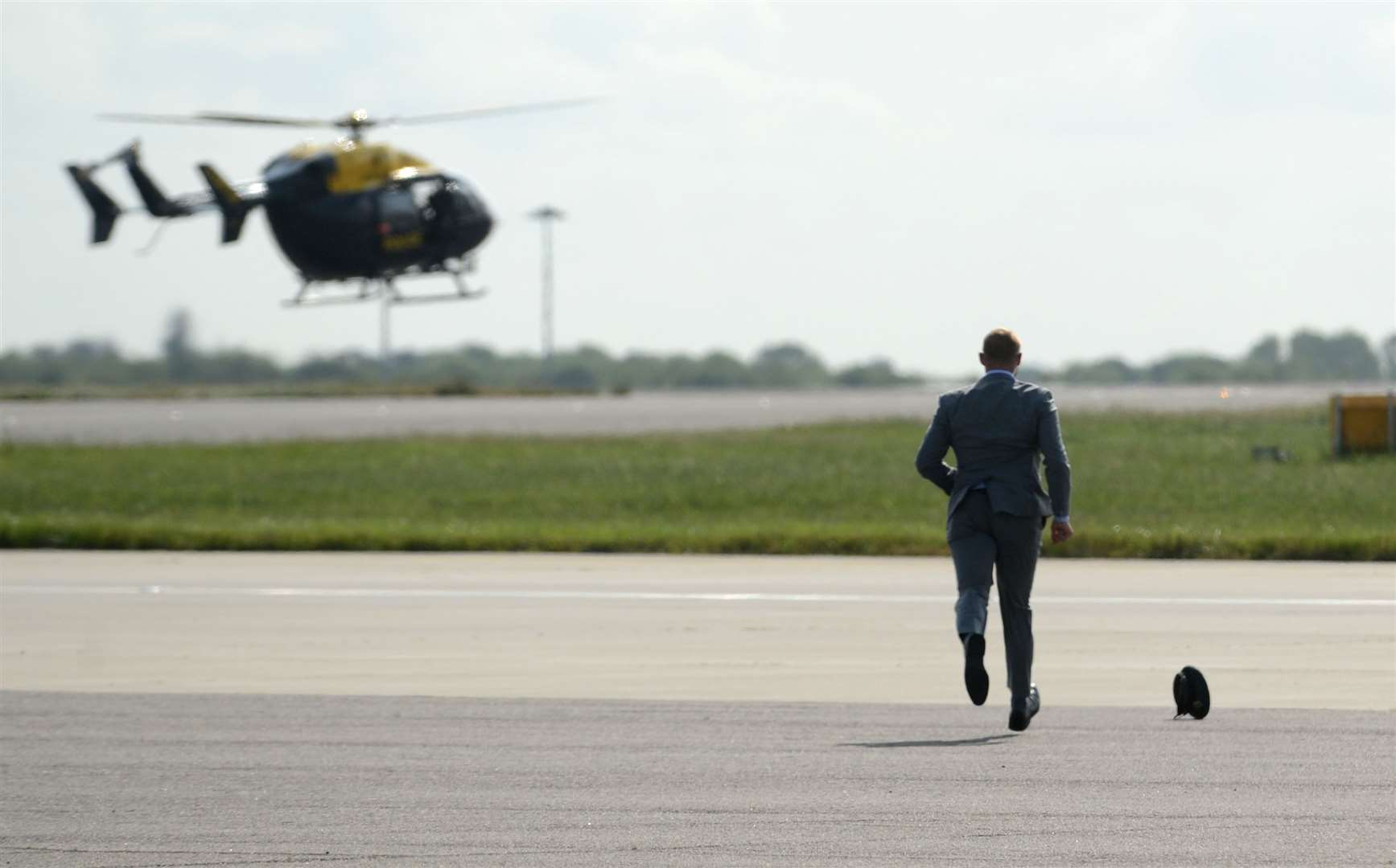 A member of the security detail chases after an RAF cap after the wind blew it off. Picture: Vikki Lince