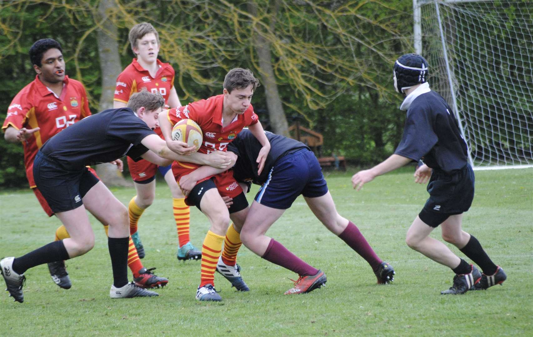 Alex Hammond taking two Holt players to stop his onslaught for Cambridge under-16s. Picture: David Bell (9382015)