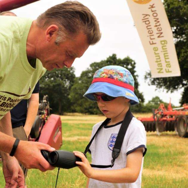 Chris Packham lends his binoculars to a young naturalist. Picture: Paul Brackley