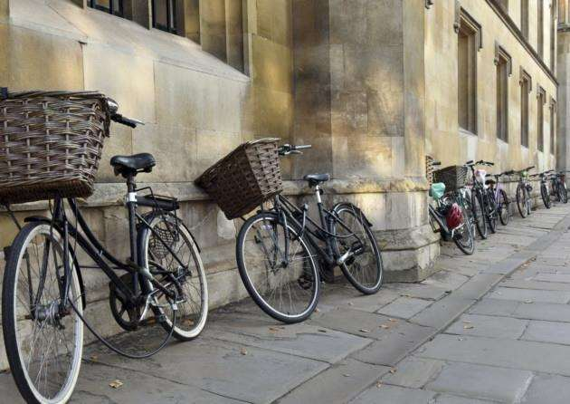 Traditional bicycles with baskets parked by students in a Cambridge street near a college. Picture by oversnap.