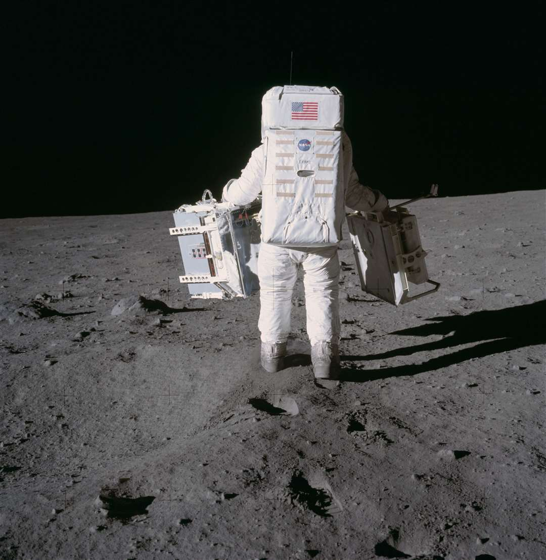 Astronaut Edwin E. Aldrin Jr., lunar module pilot, moves toward a position to deploy two components of the Early Apollo Scientific Experiments Package (EASEP) on the surface of the Moon during the Apollo 11 extravehicular activity. The Passive Seismic Experiments Package (PSEP) is in his left hand; and in his right hand is the Laser Ranging Retro-Reflector (LR3). Astronaut Neil A. Armstrong, commander, took this photograph with a 70mm lunar surface camera. Picture: NASA (14042059)