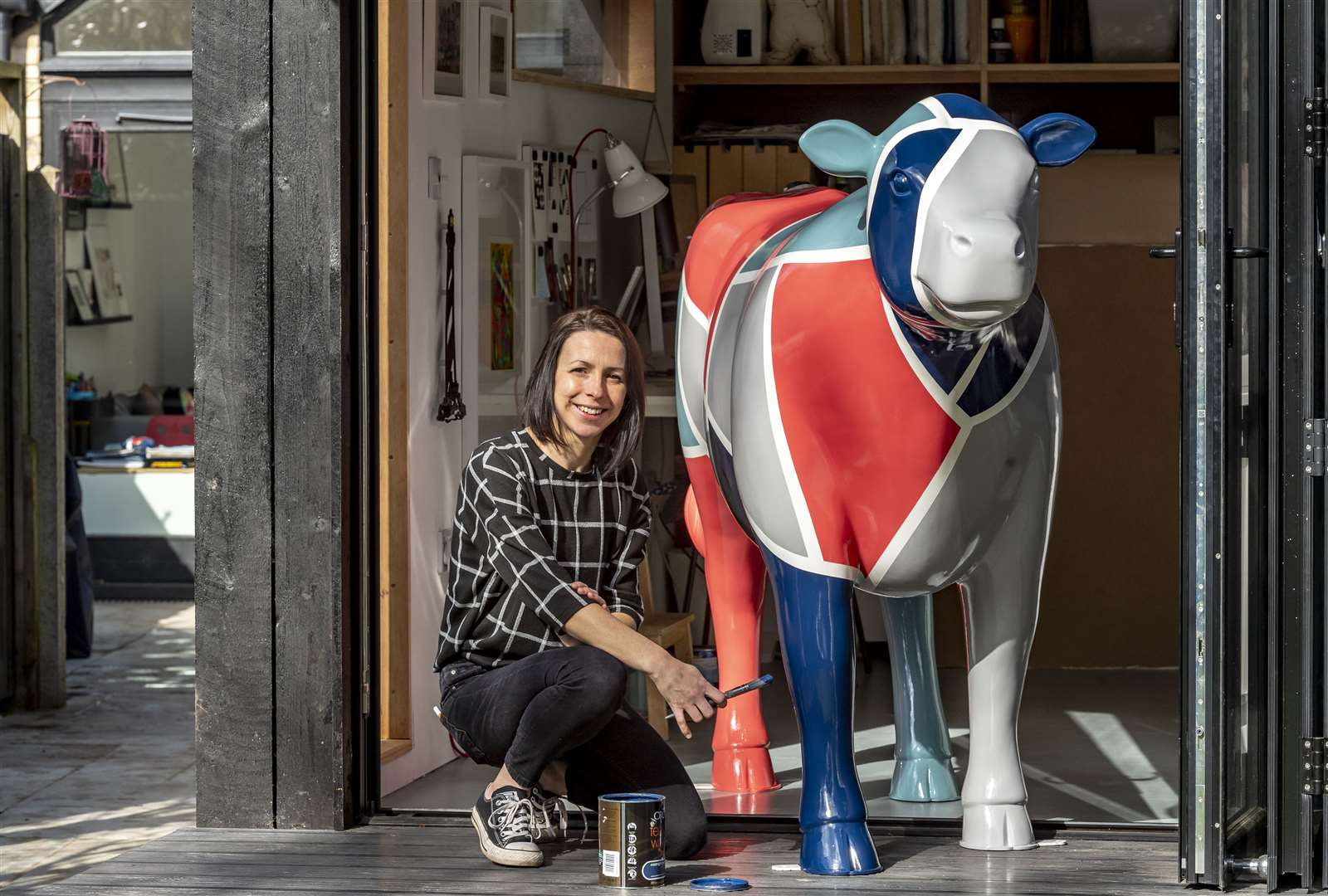 One of the 'Cows about Cambridge' artist Lucy Gough in her studio with one the painted cows. Picture: Keith Heppell. (7689696)